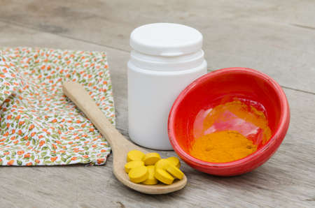Turmeric herbal tablets in white bottle ,fresh turmeric powder in wooden spoon on wooden background