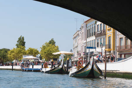AVEIRO, PORTUGAL - AUG 21, 2017: Moliceiro boats sail along the central canal in Aveiro, Portugal. Image taken from a moliceiro while we were under a bridge Editorial