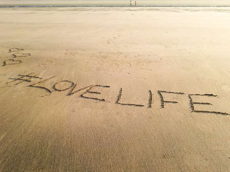 Love life written on the wet sand of Matoshinos beach.  Copy space Stock Photo - 103295694