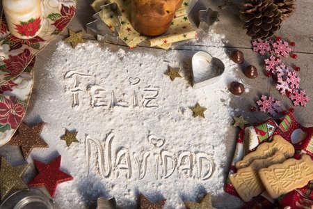 Feliz Navidad, spanish text made with flour, surrounded by Christmas decorations. Seasonal concept. Stock Photo - 107523551