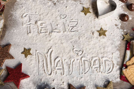 Feliz Navidad, spanish text made with flour, surrounded by Christmas decorations. Seasonal concept. Stock Photo - 107523552