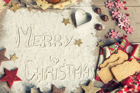 Merry Christmas, text made with flour, surrounded by Christmas decorations. Seasonal concept. Stock Photo - 107896933
