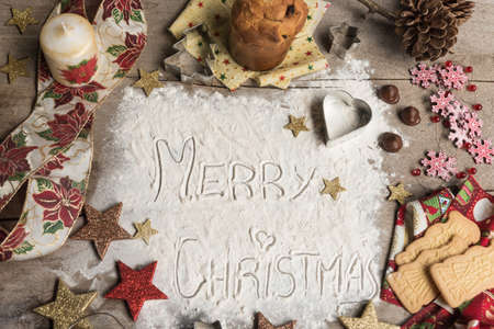 Merry Christmas, text made with flour, surrounded by Christmas decorations. Seasonal concept. Stock Photo