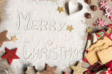 Merry Christmas, text made with flour, surrounded by Christmas decorations. Seasonal concept. Stock Photo - 107896936