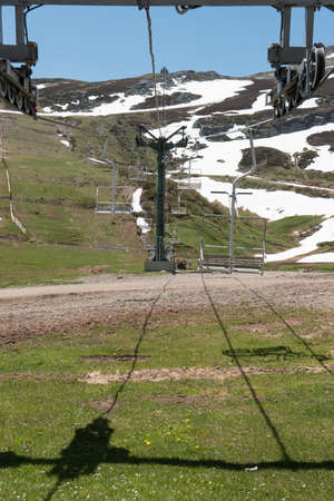 Empty chair lift on a snowy mountain during a sunny day