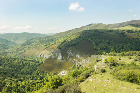 Spectacular high valley of the river Saja and its affluent the Cambillas, covered by the leafy beech woods that make up Mount Saja. All this is part of the Saja-Besaya Natural Park. Cantabria, spring time, from the viewpoint of La Cardosa. Stock Photo