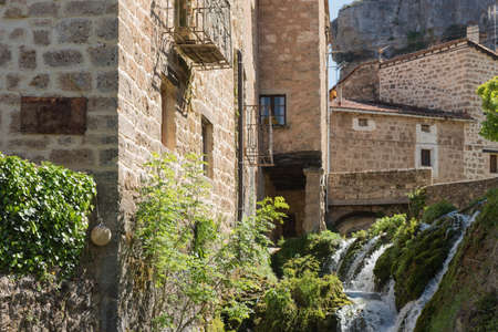 Orbaneja del Castillo, beautiful village of Burgos, Spain, crossed by a waterfall and surrounded by a range of karstic rocks with curious shapes. Stock Photo