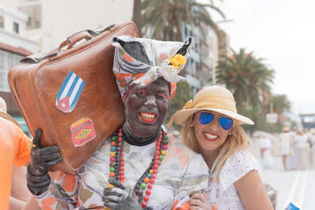 SANTA CRUZ DE LA PALMA, CANARY ISLANDS, SPAIN - MARCH 04, 2019: Man disguised as a black servant recently arrived from Cuba. Smiling woman posing with him to take a picture together. Carnival in La Palma island, festival of the Indians.