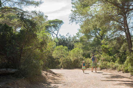Father and son walking on the roads of the island of Porquerolles,  in the south of France.