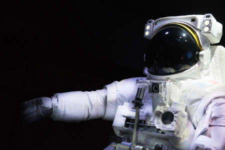 Single space Astronaut with black glas on the helmet isolated on black background