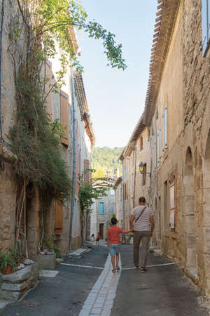 Father and son walking through the old narrow street of Lagrasse, the most beautiful medieval village of France.