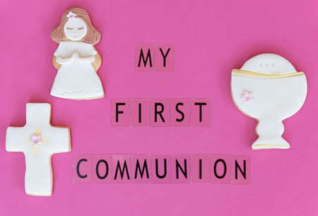 Concept: First communion. Poster announcer in English. Fondant cookies with related drawings. Pink background. Stockfoto