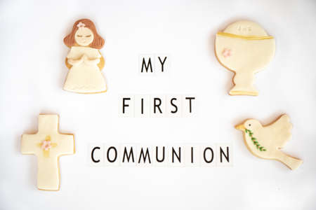 Concept: First communion. Poster announcer in English. Fondant cookies with related drawings. White background. Stockfoto