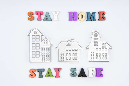 Words Stay home Stay safe made from wooden letters and three metalic houses, concept of self quarantine at home as preventative measure against corona virus Covid 19 outbreak. Staying at home during pandemic
