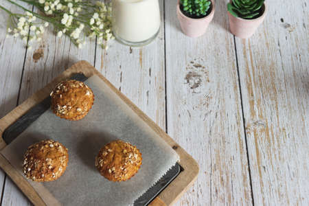Fresh homemade delicious carrot muffins decorated with oat flakes and brown sugar on rustic table, copy space, top view Stock Photo