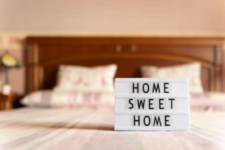 Lightbox with text: home sweet home on bed, copy space.