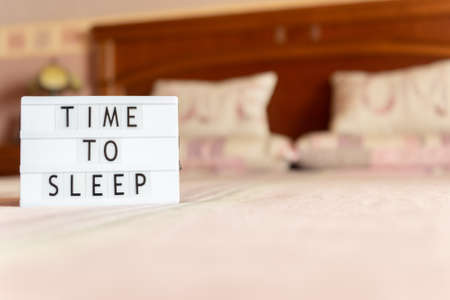 Lightbox with text: time to sleep on bed, copy space.