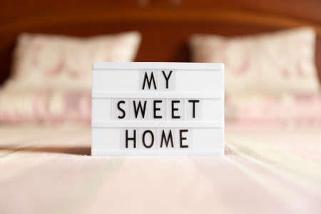 Lightbox with text: my sweet home, on the bed, copy space.