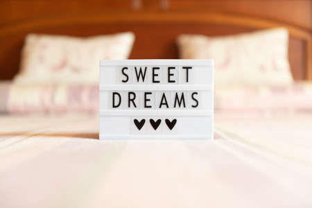 Lightbox with text: sweet dreams, on the bed, copy space.
