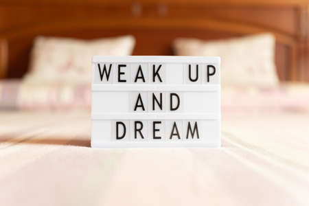 Lightbox with text: wake up and dream, on the bed, copy space.