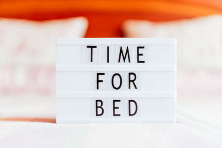 Lightbox with text: time for bed, on the bed, copy space. Фото со стока
