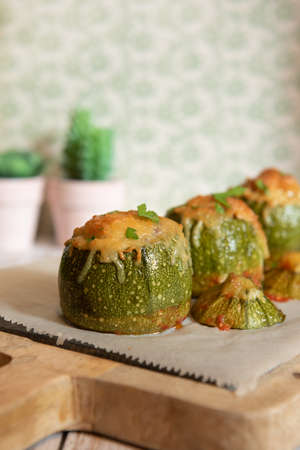 Stuffed zucchini. Round zucchini stuffed with meat and vegetables. Cheese on top