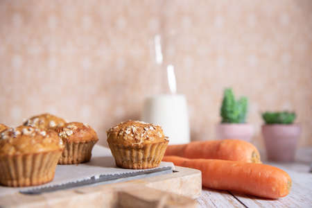 Whole grain muffins with apple, carrots and nuts on rustic cutting board on light background, Healthy vegetarian food, dairy free.