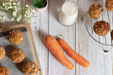 Whole grain muffins with apple, carrots and nuts on rustic cutting board on light background, Healthy vegetarian food, dairy free. Top view.