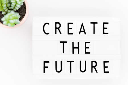 Create the future: words on lightbox on a white wooden surface, top view.