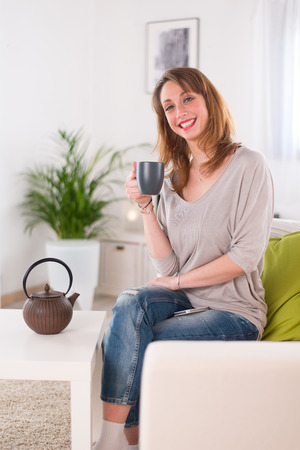 cheerful young women at home having tea and playing with her smartphone photo