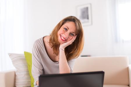 working at home: alegres mujeres j�venes en su casa trabajando en su computadora port�til Foto de archivo