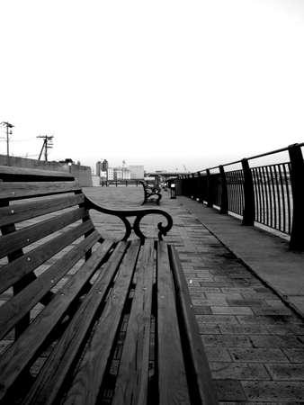 Bank en fench naast de baai van Osaka in zwart en wit