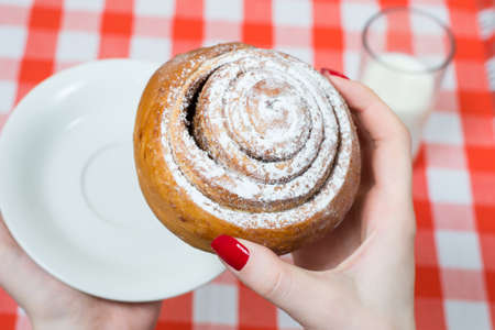 Close up, top view photo of tasty sugary cinnamon roll in womans hand