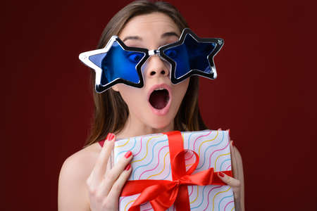 Concept of happiness when receiving presents on Christmas. Portrait of happy surprised crazy woman with open mouth. She is wearing big funny sunglasses and holding present box. Stock Photo