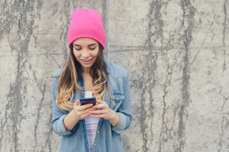 Close-up photo of smiling hipster girl reading text on smartphone. She is very happy because she got an invitation to a party