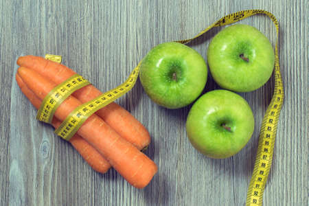 Concept of healthy nutrition. Top view photo of green fresh apples, tasty carrots and tape measure on wooden table Stock Photo