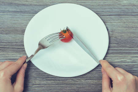 Concept of strict dieting. Woman's hands cutting little cherry tomato on empty plate