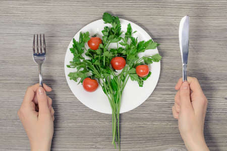 Concept of vegetarianism. Tio view  photo of wonams hands and plate with cherry tomatoes and parsley on wooden table Banco de Imagens