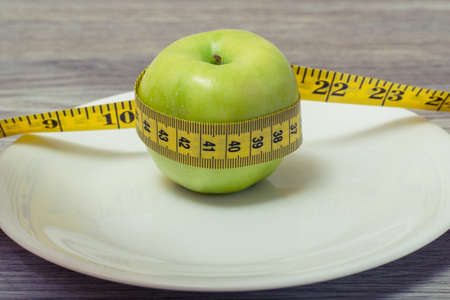 Close up photo of tape measure coiled around the apple on a white plate