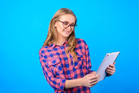 Side profile half-turned portrait of cheerful lovely sweet cute charming beautiful kind with long blonde hair manager agent checking information news on pad isolated on blue background 版權商用圖片