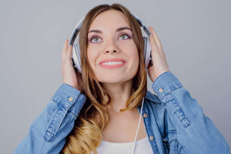 Close up portrait of girl touching white headphones with hands beaming isolated on gray background