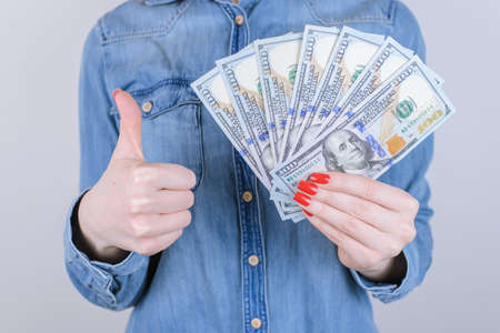 Happiness success celebrate excited satisfied good perfect great glad cool people person jeans shirt beauty customer shop concept. Cropped close up portrait of nice lady with cash isolated background Standard-Bild