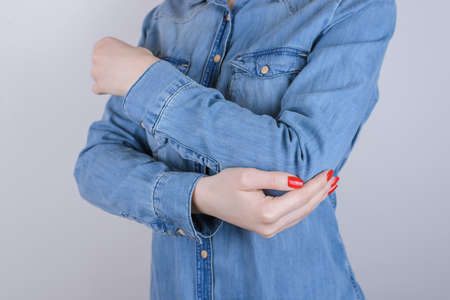 Cropped close up photo of unhappy suffering from pain lady touching elbow isolated on gray background copy-space wearing casual denim jeans clothing 版權商用圖片