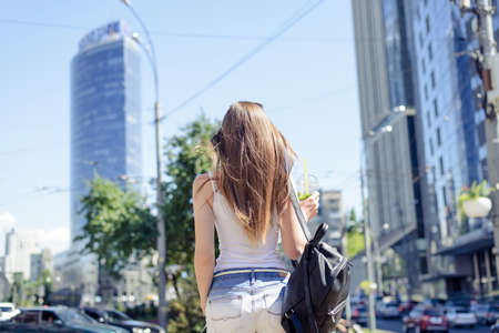 Back behind rear view close up photo portrait of pretty with long brown straight hair wearing white tank top t-shirt holding plastic cup in hand going background Imagens