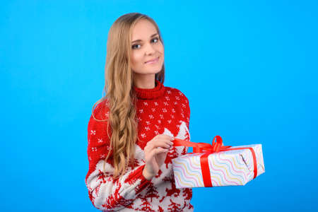 Christmas greetings and best wishes! A charming young girl is opening a giftbox from her family. She is wearing red christmas jumper, touching a ribbon to open the box in her hands. Half-turn portrait Reklamní fotografie