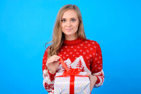 Warm wishes! Happy holidays! Cute young teenag girl is opening big giftbox from Santa Claus, she foung it under Christmas tree. She is wearing red knitted Christmas sweater.