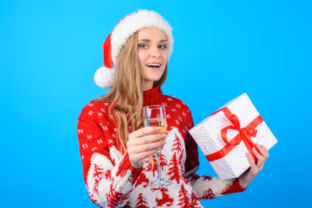 Make a wish! Portrait of smiling beautiful happy woman in red santa hat in knitted pullover, she is raising a toast and holding a present box, isolated on bright blue background