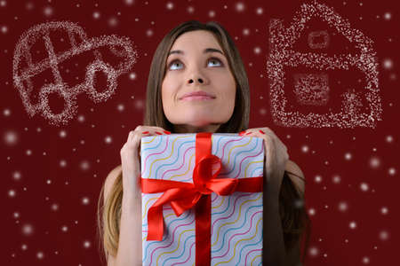 Dreams come true on Christmas. Concept of waiting for miracle on holidays. Happy minded woman with a giftbox in hands is dreaming about new house and a car. Isolated on red background