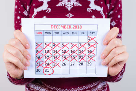 Its five days to new year! Close up of calendar in womans hands isolated on grey background Stock Photo