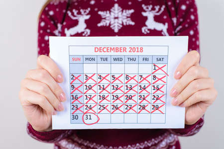 Its one day to new year! Cropped close up photo of calendar holding woman in hands isolated on grey background